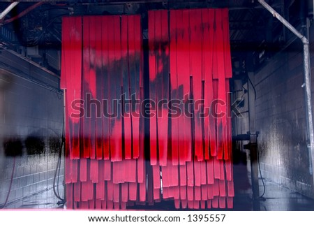 Entering the soft cloth car wash tunnel before the automatic system starts spraying.  Interior of the car wash viewed from inside the car.  The red cloths are hanging with black grime on them. - stock photo