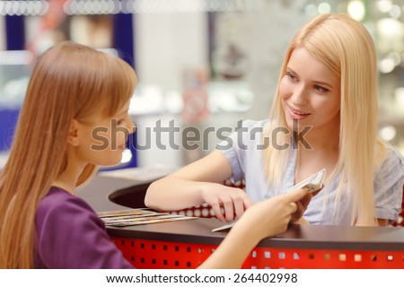 Entertainment opportunities in big shopping mall. Close-up of a pretty female customer asking for information on the help desk of a shopping mall - stock photo