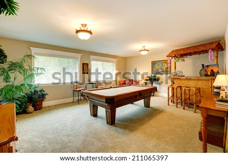 Entertainment room in hawaian style with pool table, crafted wooden bar with rustic stools and palm trees