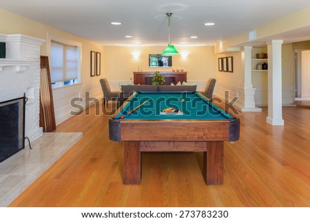 Entertainment Room with fire place, wooden floor and pool billiard in luxury home.   - stock photo