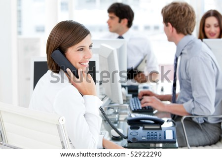 Enthousiastic businesswoman talking to the phone in the open-space - stock photo