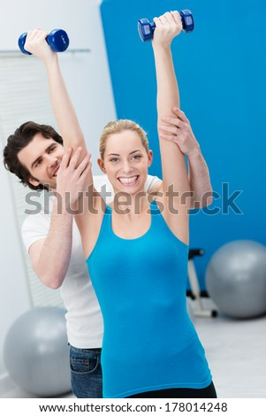Enthusiastic beautiful woman working out in the gym with the aid of a handsome male fitness instructor raising her dumbbells above her head and extending her arms - stock photo