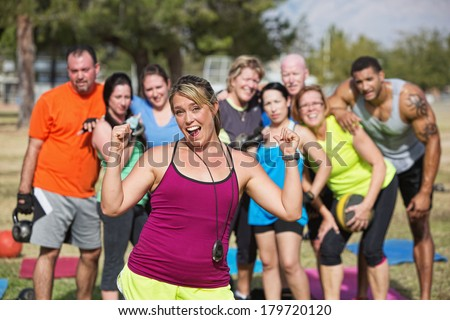 Enthusiastic  bootcamp fitness instructor with group outdoors - stock photo
