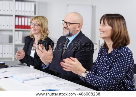 Enthusiastic business team clapping their hands in congratulations at the end of a business presentation in the office as they sit together at a table - stock photo