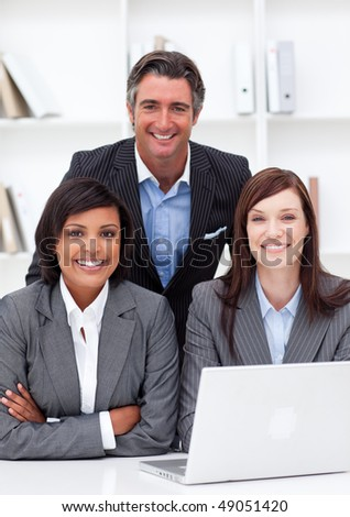 Enthusiastic businesswomen and their colleague working at a laptop in the office - stock photo