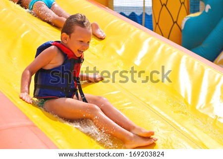 Enthusiastic children on slide in the waterpark - stock photo