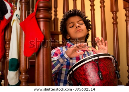 Enthusiastic darkskinned boy playing drum. Kid plays drum on stairs. His inspiration is limitless. Let the music flow. - stock photo