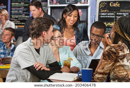 Enthusiastic diverse group of students with textbook in cafe - stock photo
