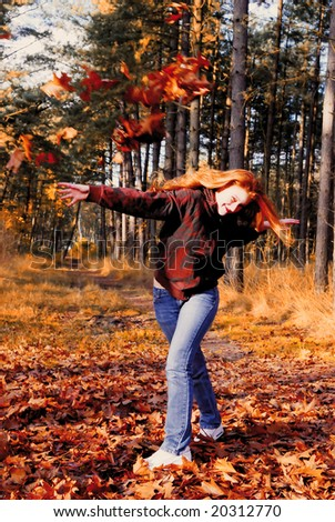 Enthusiastic dutch girl throwing with autumn leaves in the forest - stock photo