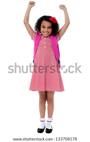 Enthusiastic elementary school girl posing with arms raised up, victorious. - stock photo