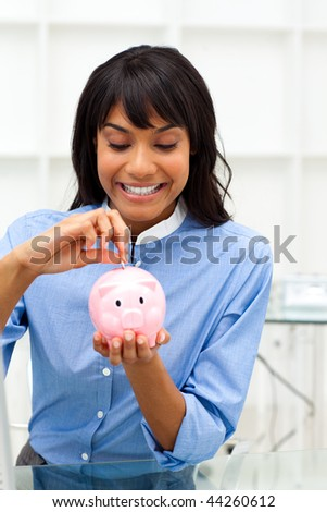 Enthusiastic ethnic businesswoman saving money in a piggybank in the office - stock photo