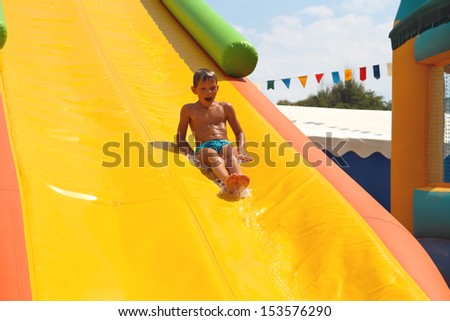 Enthusiastic kid on slide in the waterpark - stock photo