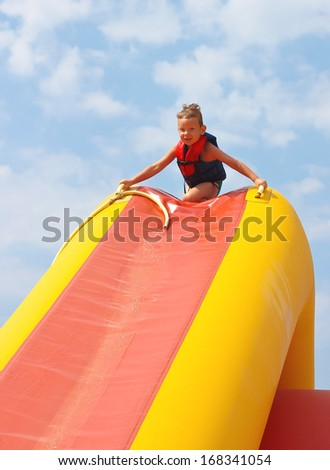 Enthusiastic kid on slide in the waterpark