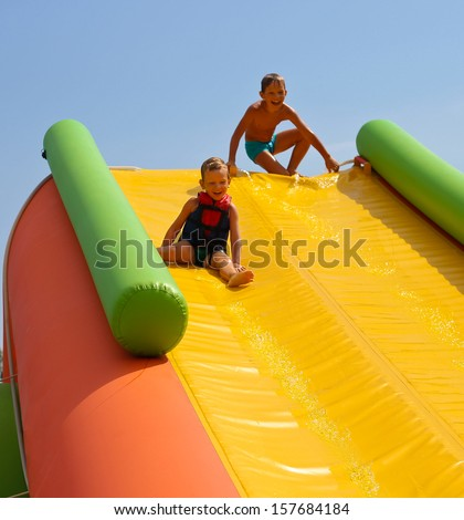 Enthusiastic kids on slide in the water park - stock photo