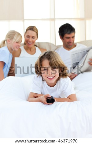 Enthusiastic little boy holding a remote  lying on the bed - stock photo