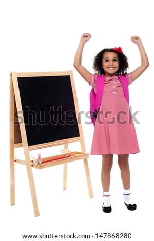 Enthusiastic little school girl in uniform - stock photo