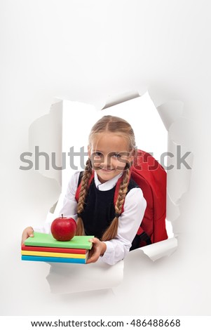 Enthusiastic little schoolgirl ready for school - bursting out from a white paper layer, copy space