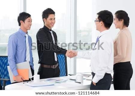 Enthusiastic partners shaking hands in office over signed papers