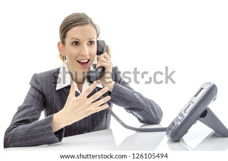 Enthusiastic woman at office desk talking on the phone. Isolated on a white background.