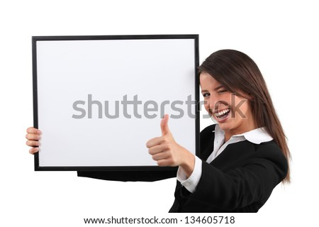 Enthusiastic woman giving the thumb's up and holding a whiteboard - stock photo
