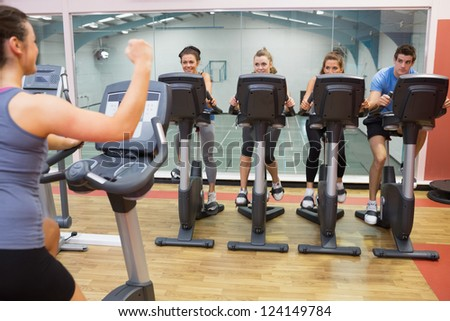 Enthusiastic woman teaching spinning class to four people at the gym - stock photo