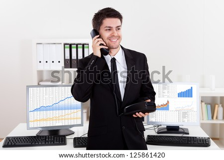 Enthusiastic young male stock broker in a bull market holding a telephone - stock photo