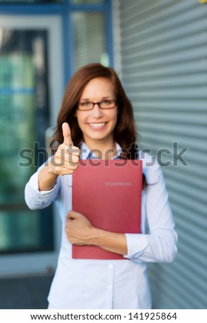 Enthusiastic young woman clutching a red folder giving a thumbs up of approval and success with focus to her hand - stock photo