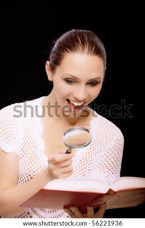 Enthusiastic young woman reads book through magnifier, on black background. - stock photo