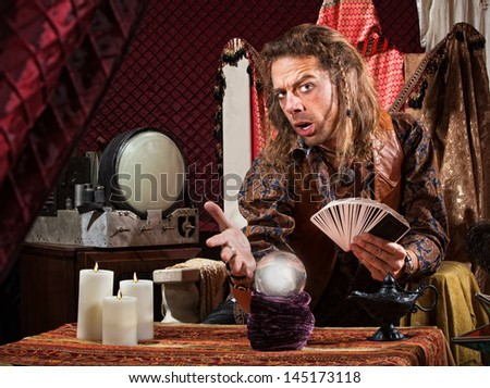 Enticing man with tarot cards and crystal ball - stock photo