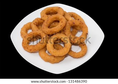 Entire plate of onion rings over black background - stock photo