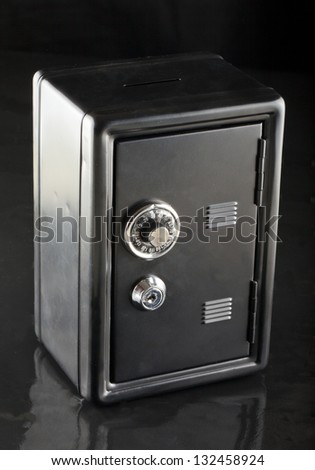 Entire view of a black strongbox over black background - stock photo