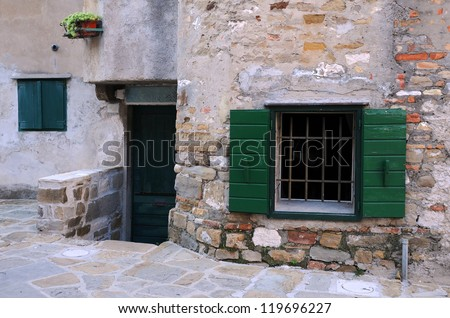 Entrance and windows with shutters in the town of Grado in Italy