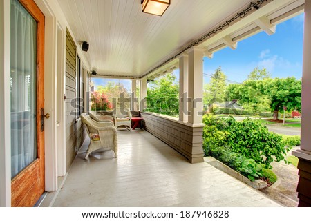 Entrance column porch with wicker chairs - stock photo