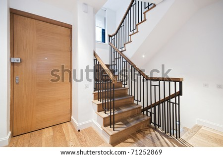 entrance door and modern staircase with a nice wooden finish - stock photo