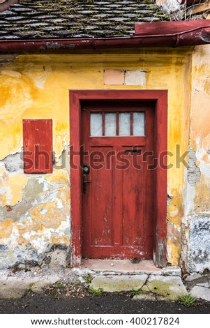 Entrance door of a dilapidated old rural house with shabby facade. Beautiful retro.