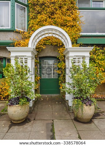 Entrance door with arc decorated with ivy in autumn colors - stock photo
