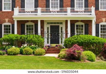 Entrance doorway to large single family modern US house with landscaped gardens and lawn on a warm sunny summers day - stock photo