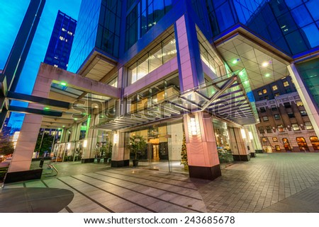 Entrance, fragment  to the building lobby. Night scene of colorful city life with skyscrapers, highrise buildings. Vancouver downtown  at night. - stock photo