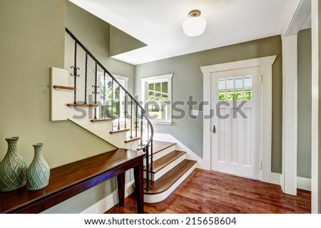 Entrance hallway with staircase and table. View of steps with wrought iron railings - stock photo
