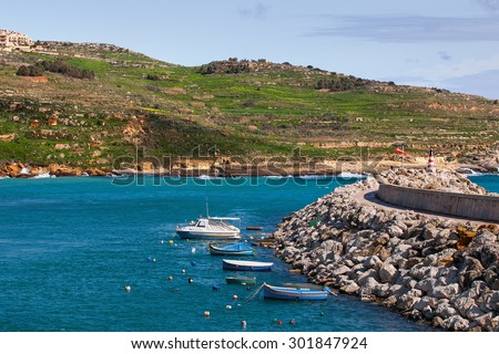 Entrance in bay, seafront with lighthouse on seafront. Gozo island, Malta. - stock photo