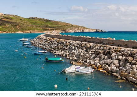 Entrance in bay, seafront with lighthouse on seafront. Gozo, Malta. - stock photo