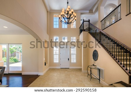 Entrance Mansion Interior with staircase in large private home with granite floor and large chandelier and staircase.  - stock photo