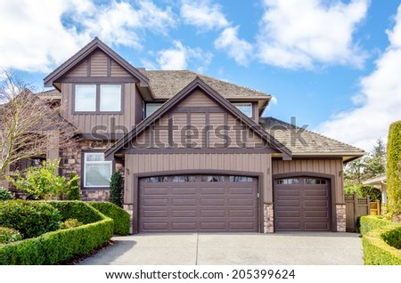 Entrance of a luxury house with a patio and a two-car garage on a bright, sunny day. - stock photo
