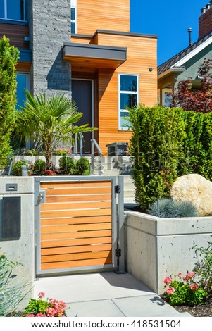 Entrance of new luxury family house with landscaped front yard. Modern residential house with concrete pathway through the gate - stock photo