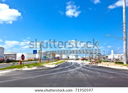 entrance of refinery with tanks - stock photo