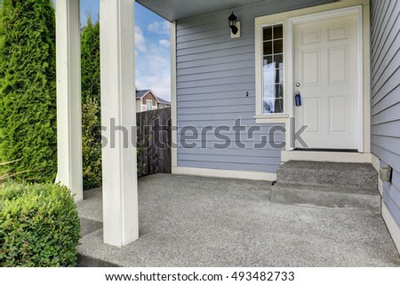 Entrance Porch With Concrete Floor And Square Columns. Exterior Of Large  Blue House. Northwest