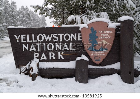Entrance sign for Yellowstone National Park on a snowy spring day
