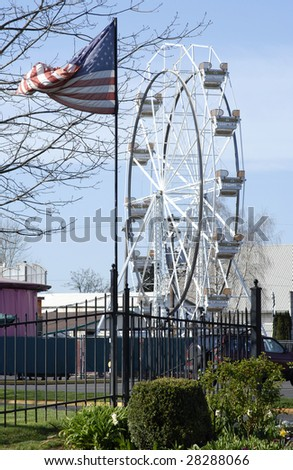 Entrance to an amusement park, with American flag and ferris wheel. All American Summer of Fun. - stock photo