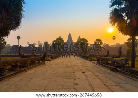 Entrance to Angkor Wat at sunrise. Road to the historic Ruins in Siem Reap, Cambodia.. - stock photo