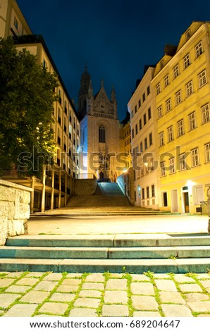 Entrance to Maria am Gestade gothic church in Vienna, Austria. Long stairs to leading to it among neat buildings. Warm summer night
